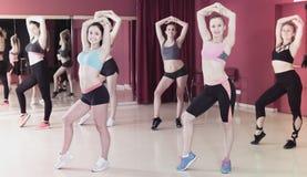 Smiling active women exercising dance moves stock photos
