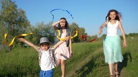 Smiling adolescent girls with child waving with colored ribbons and enjoy vacation outdoors. Near loch stock footage