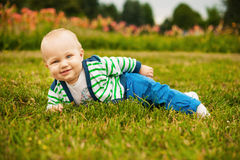 Smiling adorable baby looking at camera outdoors in sunlight Royalty Free Stock Photo