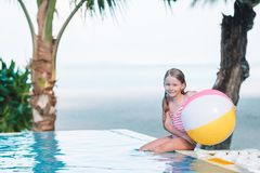 Smiling adorable girl playing with inflatable toy ball in outdoor swimming pool. Happy kid playing with inflatable toy ball in outdoor swimming pool on Maldives royalty free stock images