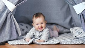 Smiling adorable little baby lying relaxing at home having positive emotion full shot. Happy laughing cute child having fun in cozy interior looking at camera stock footage