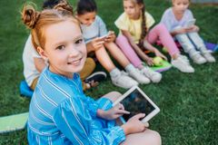 smiling adorable schoolgirl using tablet while sitting on grass stock images