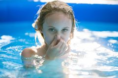 Smiling adorable seven years old girl playing and having fun in inflatable pool stock image