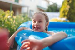 Smiling adorable seven years old girl playing and having fun in inflatable pool.  royalty free stock photo