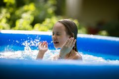 Smiling adorable seven years old girl playing and having fun in inflatable pool.  royalty free stock image