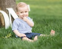 A smiling adorable small baby boy holding a finger in his mouth sitting on green grass outdoor at summer park. Emotions, smile, su. Rprised, kid, toddler, sly Royalty Free Stock Photo