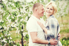 Smiling adult couple at blossom apple orchard Royalty Free Stock Image
