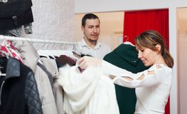 Smiling adult couple choosing clothes. At clothing shop stock photo