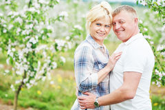 Smiling adult couple in love. Blossoming tree garden Stock Photo