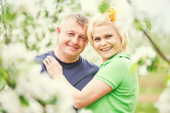 Smiling adult couple in love. Blossoming tree garden Stock Image