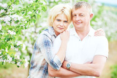Smiling adult couple in love. Blossoming tree garden Royalty Free Stock Image