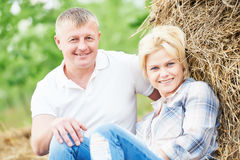 Smiling adult couple near haystack at countryside Royalty Free Stock Images