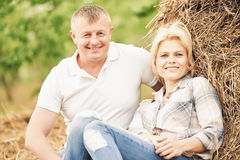 Smiling adult couple near haystack at countryside Stock Photos