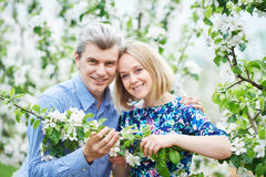 Smiling adult couple portrait in blossoming apple tree garden Royalty Free Stock Photos
