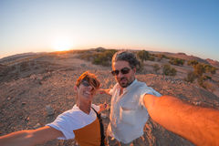 Smiling adult couple taking selfie in the Namib desert, Namib Naukluft National Park, main travel destination in Namibia, Africa. Fisheye view in backlight Stock Photo