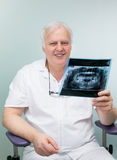 Smiling adult dentist with xray Stock Images