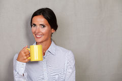 Smiling adult female holding hot drink Royalty Free Stock Image