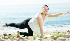 Smiling adult female in white T-shirt is stretching Royalty Free Stock Photos