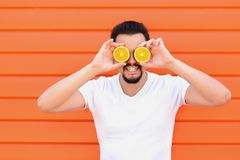 Smiling adult man with beard and moustache in white shirt pose standing against against wall covering eyes with two sliced oranges stock photography