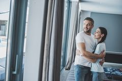 Smiling adult man hugging attractive girlfriend. At home royalty free stock photography