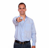 Smiling adult man pointing with remote control Royalty Free Stock Photography