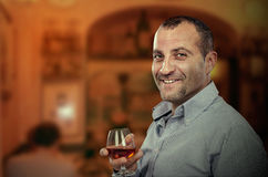Smiling adult man posing with glass of brandy Stock Photo