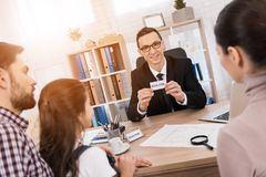 Smiling adult man shows card with inscription by realtor. Concept of real estate sales. House for sale. royalty free stock photos