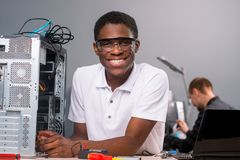 Technician in safety glasses. Smiling adult in safety glasses looking at the camera, holding an analogue multimeter. Laptop and screwdrivers on the table. Happy Stock Photos