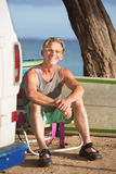Smiling Adult Sitting with Surfboard Royalty Free Stock Images
