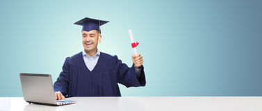 Smiling adult student in mortarboard with diploma. Education, graduation, business, technology and people concept - happy adult student in mortarboard with Stock Photo
