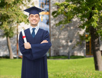Smiling adult student in mortarboard with diploma. Education, graduation and people concept - smiling adult student in mortarboard with diploma over campus Stock Photography