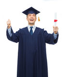 Smiling adult student in mortarboard with diploma royalty free stock image