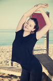 Smiling adult woman in black T-shirt is practicing stretching Royalty Free Stock Images