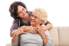 Smiling adult woman embracing senior mother Royalty Free Stock Images