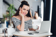 Smiling adult woman sitting in a cafe with a laptop, holding a cup of coffee and looking at the camera. Royalty Free Stock Photo
