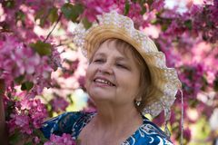 Smiling adult woman wearing a hat under pink. Beauty adult woman under pink flowers in summer Royalty Free Stock Image
