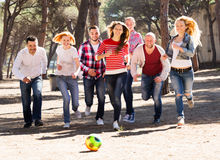 Smiling adults chasing ball outdoors Stock Image