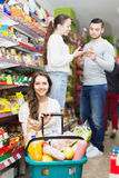 Smiling adults choosing tinned food Royalty Free Stock Images