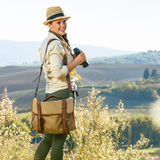 Smiling adventure woman hiker hiking in Tuscany with binoculars Stock Images