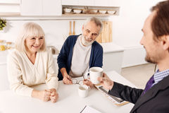 Smiling advisor enjoying conversation with aging couple of clients Royalty Free Stock Images