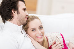 Smiling affectionate woman cuddling her husband Stock Photos