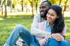Smiling african american boyfriend hugging girlfriend. In park royalty free stock photo