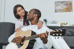 smiling african american boyfriend playing guitar for girlfriend stock photo