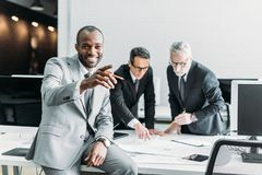 smiling african american businessman pointing away while business colleagues discussing work stock photos