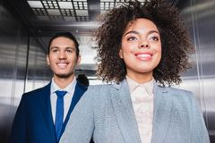 Smiling african american businesspeople riding. An elevator stock photo