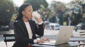 Smiling African American businesswoman sitting in cafe on the summer terrace, drinking coffee and working on the laptop stock footage
