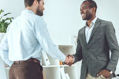 Smiling african american and caucasian businessmen. Shaking hands royalty free stock photography
