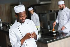 Smiling african american chef using smartphone. At restaurant kitchen royalty free stock photography