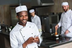 Smiling african american chef using smartphone at restaurant kitchen and looking. At camera royalty free stock photography