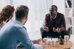 Smiling african american counselor talking to young couple. In office stock photo